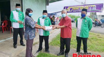 SUMBANGAN : Mohd Kamil menyampaikan sumbangan kepada wakil penerima.