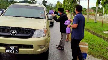 SELAMAT BERPUASA: Abu Bakar edarkan bungkusan manis berbuka puasa kepada pengguna jalan raya