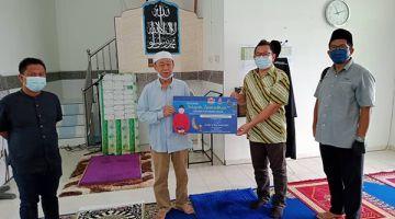 PRIHATIN: Abu Bakar (dua kanan) menyampaikan sumbangan Bung kepada salah satu wakil Masjid Al Jihad Pekan Bukit Garam sambil diperhatikan oleh Pegawai Kemajuan Masyarakat DUN Lamag Rozamsah Ismail (kiri) dan Penyelia UPPM Lamag Shopian Nasir (kanan)