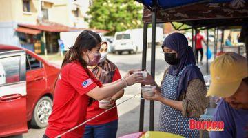 EDAR: Vivian (kiri) mengedarkan bubur lambuk kepada penduduk sekitar Sandakan.