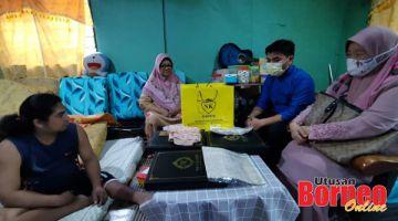 BAJU RAYA : Sapiah (dua kiri) menerima sumbangan baju raya daripada  NK Gallery Tawau.