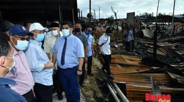 PRIHATIN: Hajiji (tiga kiri) melawat lokasi kebakaran di Kg Meruntum, turut kelihatan ialahMenteri Pembangunan Masyarakat dan Kesejahteraaan Rakyat Sabah, Shahelmey Yahya (empat kiri) yang juga Ahli Dewan Undangan Negeri (ADUN) Tanjung Keramat.