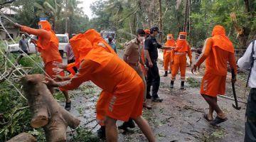KERJA MEMBERSIH: Gambar serahan oleh Pasukan Respons Bencana Antarabangsa (NDRF) menunjukkan kakitangan NDRF bertungkus lumus mengalihkan pokok tumbang di atas jalan raya selepas dibadai Siklon Tauktae di Margao, Goa, kelmarin. — Gambar AFP