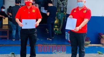 BERSIH NAMA: Kuan San (kanan) bersama Dr Rayong menunjukkan laporan polis dan lampiran bahan bukti selepas membuat laporan polis di Balai Polis Sungai Maong pagi semalam.