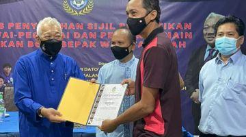 TAHNIAH: Bung menyampaikan watikah pelantikan kepada salah seorang pegawai pasukan Bola Sepak Wanita Sabah.