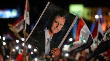 PILIHAN RAKYAT: Penyokong membawa gambar potret Presiden Syria yang baharu, Bashar al-Assad selepas beliau memenangi pilihan raya di Syria. — Gambar AFP