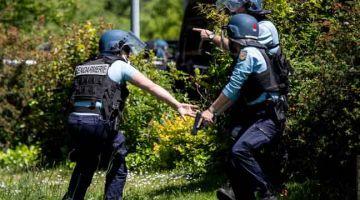 TUMPAS: Anggota polis Perancis menghendap kawasan yang dipercayai tempat suspek bersenjatakan pisau bersembunyi selepas insiden serangan ke atas seorang anggota polis di La Chapelle-sur-Erdre. — Gambar AFP