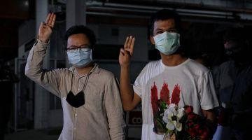 BEBAS: Anon Numpa (kiri) dan Panupong Jadnok menunjukkan tiga jari ketika meninggalkan Hospital Universiti Thammasat, selepas kedua-dua ketua protes prodemokrasi itu dibebaskan dengan ikat jamin ekoran dijangkiti COVID-19 ketika dalam penahanan praperbicaraan di Penjara Reman Bangkok kelmarin. — Gambar AFP