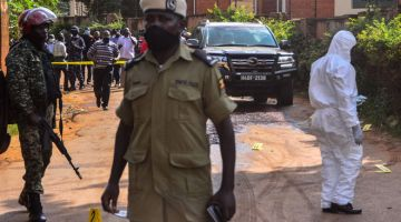 PERIKSA: Anggota polis memeriksa kawasan di mana kenderaan Wamala diserang empat suspek menunggang motosikal yang membunuh anak perempuannya dan seorang pengawal peribadi di Kampala, Uganda kelmarin. — Gambar AFP
