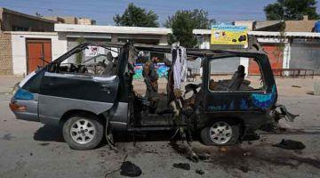 MUSNAH: Anggota keselamatan dilihat berdiri berhampiran kenderaan yang musnah dalam letupan bom di Kabul, Afghanistan kelmarin. — Gambar AFP
