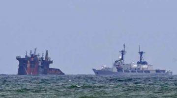 HANGUS: Sebuah kapal (kanan) kelihatan menghampiri kapal MV X-Press Pearl yang separuh karam selepas dijilat api selama hampir dua minggu di luar pelabuhan Colombo, Sri Lanka semalam. — Gambar AFP