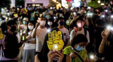 ACARA PERINGATAN AWAM: Penduduk menyalakan lampu telefon bimbit dan menyalakan lilin di sekitar bandar di Hong Kong sebagai menandakan tarikh tersebut. — Gambar AFP
