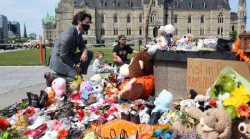 TRAGEDI MEMILUKAN: Gambar fail pada 1 Jun 2021, kelihatan Trudeau mengunjungi memorial sementara susulan penemuan rangka tulang 215 kanak-kanak di dalam kubur tidak bertanda di Kamloops Indian Residential School di  British Columbia. — Gambar AFP