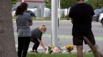 TURUT BERSIMPATI: Seorang wanita meletakkan bunga di simpang jalan di mana seorang lelaki memandu trak pikap dengan sengaja melanggar dan menyebabkan kematian empat anggota keluarga Islam di London, Ontario kelmarin. — Gambar AFP