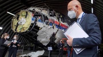 SIASAT: Gambar dirakam pada 26 Mei lalu menunjukkan hakim dan peguam berdiri di sebelah serpihan pesawat MH17 yang dibina semula semasa memeriksa petunjuk mengenai nahas                 pesawat tersebut. — Gambar AFP
