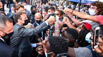 MESRA: Marcon (kiri) menyapa orang ramai ketika mengadakan lawatan kerja ke Valence                         di Drome, tenggara Perancis. — Gambar AFP