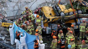 TRAGIS: Anggota penyelamat menggeledah runtuhan untuk mencari mangsa terselamat selepas sebuah bangunan yang sedang dalam proses diroboh tiba-tiba runtuh dan menimpa sebuah bas di Gwangju, Korea Selatan kelmarin. — Gambar AFP