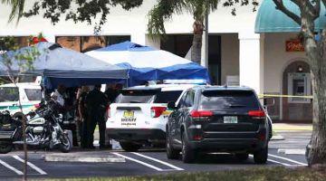 SIASAT: Pegawai syerif Palm Beach County berdiri di luar kedai runcit Publix di Florida di mana seorang wanita, seorang lelaki dan seorang kanak-kanak ditemui mati kelmarin. — Gambar AFP