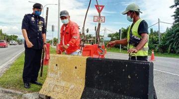 PANTAU: Haris memantau pemasangan hadangan konkrit di pusingan U Jalan Penampang Bypass Kota Kinabalu- Penampang.