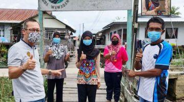 Siti Suraya (tengah) dan ibubapanya, Najor (kanan) ketika ditemui Abdullah di Kampung Semop, pada Sabtu.