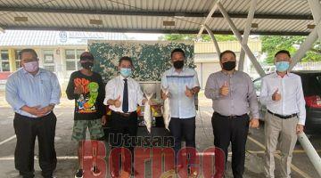 KENANGAN:Joachim (tiga kiri) bersama Fadzil Anthony (tiga kanan) mewakili Alkarim Mussapa  merakamkan gambar kenangan di Wisma Kewangan, Kota Kinabalu