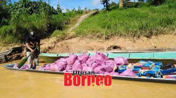 AGIH BANTUAN: Jurugan perahu panjang mengangkut bantuan makanan untuk diagihkan  di kawasan pedalaman Machan.