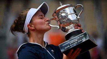 UNGGUL: Krejcikova mencium trofinya selepas menewaskan Pavlyuchenkova pada final Terbuka Perancis di Paris. — Gambar AFP