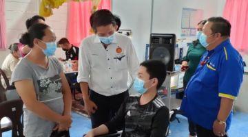 Dennis (tengah) bercakap dengan seorang penerima vaksin di PPV Klinik Kesihatan Long San, semalam.