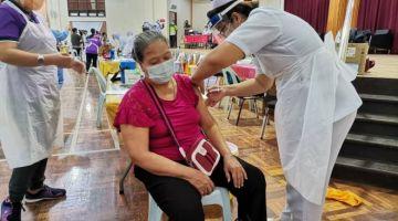 Salah seorang warga emas wanita menerima suntikan vaksin COVID-19 di PPV Dewan Masyarakat Tebedu.