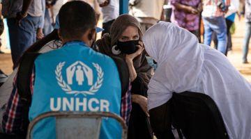 PRIHATIN: Angelina Jolie bercakap dengan pelarian Mali ketika berada di Goudebo, sebuah kem yang menerima lebih daripada 11,000 pelarian di Burkina Faso, pada Hari Pelarian Sedunia pada 20 Jun lepas.  — Gambar AFP