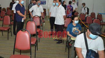 NGABAS: Dr Rundi (kanan) enggau Syazwan, Peter, Dr Melvin sereta bala bukai lebuh ke ngabas proses vaksinasyen di PPV Industri di Kelab Kidurong Bintulu.