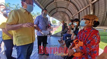 MERI PENERANG: Dr Sim meri penerang ngagai raban orang lunggar umur Flat KMC ti ngena bas maya datai betuchuk vaksin di PPV Klinik Pengerai Tanah Putih. — Gambar Roystein Emmor