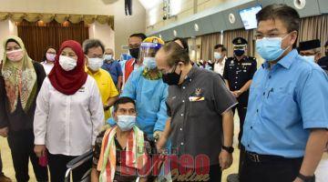 KERINGKA SEMENGAT: Uggah (dua kanan) enggau Jamilah (kiri) sereta Dr Sim meri jaku peransang ngagai siku orang lunggar umur ti deka betuchuk vaksin ba PPV Dewan Suarah Lundu.