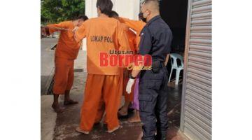 Suspek (berselipar) berselindung di sebalik beberapa tahanan lain untuk mengelak wajahnya dirakam oleh pihak media.