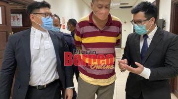 Peguam Daniel (kanan) dan Jackson (kiri) menjelaskan mengenai kes tersebut kepada tertuduh (tengah) semasa berada di lobi Mahkamah Kuching, hari ini.