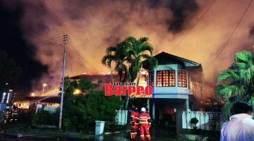 API MARAK: Anggota bomba berusaha memadam kebakaran membabitkan dua rumah di kawasan Teck Guan Villa.