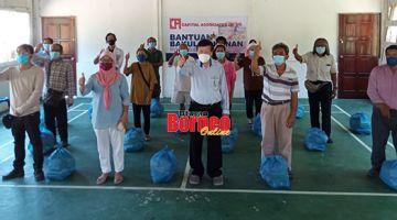 KENANGAN: Ling (tengah) merakamkan gambar kenangan bersama para penerima bantuan