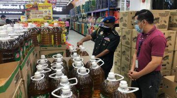 Mogan (kiri) memeriksa harga runcit maksimun bagi minyak masak sawit tulen di sebuah pasar raya di Kuching.