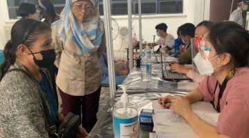 Fatimah (tengah) melihat sendiri proses pemberian vaksin kepada seorang gelandangan di PPV Stadium Perpaduan Sarawak, hari ini.