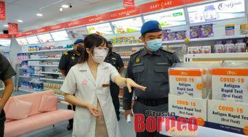 Kelyn (kanan) memeriksa RTK antigen COVID-19 di sebuah farmasi di Jalan Central di sini, sambil menerima penerangan daripada pegawai farmasi berkenaan, Michelle Chieng.
