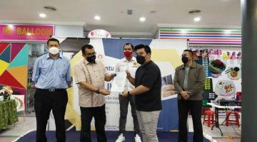 Hasbi (dua kiri) menyerahkan Surat Tawaran Pembiayaan Perniagaan Prihatin Mikro kepada salah seorang usahawan di Kuching. Turut kelihatan Azmi (dari kiri), Fazzrudin dan Mohd Syafiq.