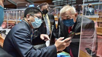 TELITI: Bung (kanan) sempat meneliti isu yang dibincangkan bersama ADUN Kadamaian Datuk Ewon Benedick (kiri).