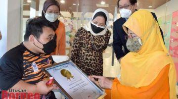 Fatimah melihat sijil pengiktirafan Malaysia Book Of Records kepunyaan Bonnie. -Gambar oleh Roystein Emmor