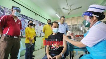 Dr Muhamad Irfan (kiri), Wee (belakang, kanan) dan tetamu kehormat lain menyaksikan petugas barisan hadapan perubatan menerima dos vaksin penggalak. -Gambar Chimon Upon