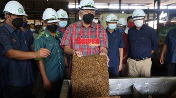 LAWATAN: Mahdzir (tengah) menunjukkan produk getah yang diproses semasa melawat kilang berkenaan.