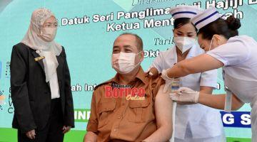 DOS PENGGALAK: Hajiji (tengah) menerima suntikan vaksin dos penggalak sempena dengan program itu.