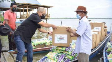PRIHATIN: Ronald (kiri) menyampaikan bantuan MAFI Prihatin kepada wakil penduduk kampung di kawasan pulau di Beluran.