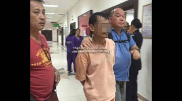 DIBICARAKAN: Tertuduh (berpakaian warna oren) diiringi dua anggota polis ke bilik perbicaraan.