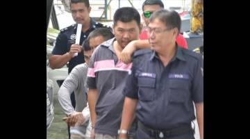 DIDAKWA: Hii (dua kanan) diiring anggota polis selepas didakwa di Mahkamah Majistert atas tuduhan membunuh.