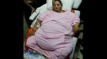 TERLAMPAU BERAT: Wanita Mesir, yang sudah menjalani pembedahan  mengurangkan berat badan pada Mac lalu, diusung keluar dari hospital di Mumbai, India kelmarin. — Gambar Reuters